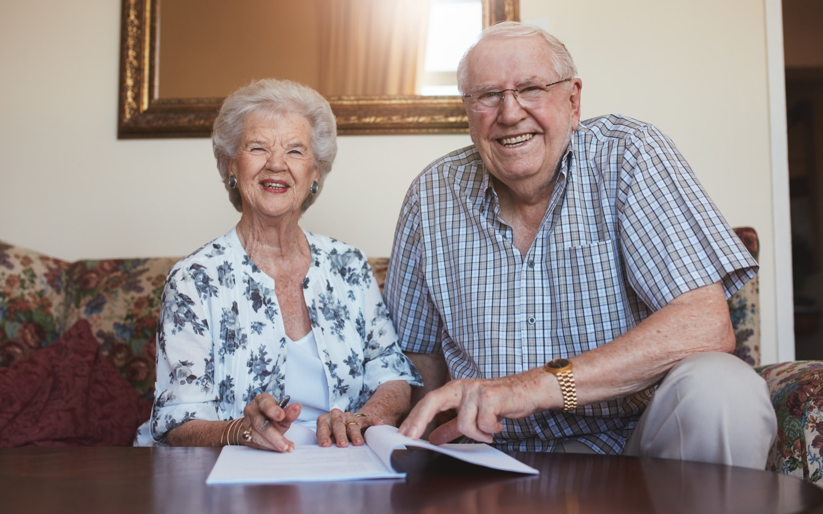 Elderly couple signing documents
